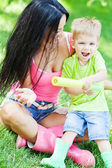 Young mother and her little son outdoors in colorful rubber boots — Stockfoto
