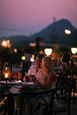 Beautiful couple eating at restaurant outside — Stock Photo