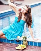 Woman in blue dress relaxing near pool — Stockfoto