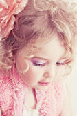 Beautiful young blond female child with curly hair posing in studio — Stock Photo