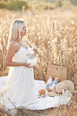 Blond woman in white dress with milk on nature — Stok fotoğraf