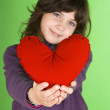 Stock Photo: Happy little girl with red valentines heart