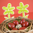 Easter eggs in wicker basket on red background - Stock Photo