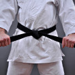 Stock Photo: Min martial arts uniform holding his black belt with both hands