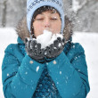 Beautiful woman blowing in the snow  — Stock Photo