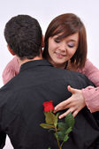 Happy beautiful teenage couple, a boy giving a rose to his girlfriend — Stock Photo