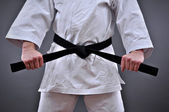 Man in martial arts uniform holding his black belt with both hands — Stock Photo