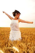 Young beautiful girl jumping in the middle of the cornfield — Stock Photo