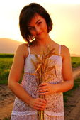 Beautiful young girl with wheat in her hand — Stock Photo