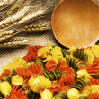 Tricolor Pasta fusilli pile on burlap — Stock Photo