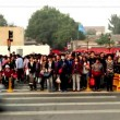 Stock Video: Crowded visitors cross street in spite of traffic light