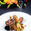 Juicy roe steak on a plate and glass of red wine - Stock Photo