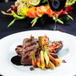 Juicy roe steak on a plate and glass of red wine - ストック写真
