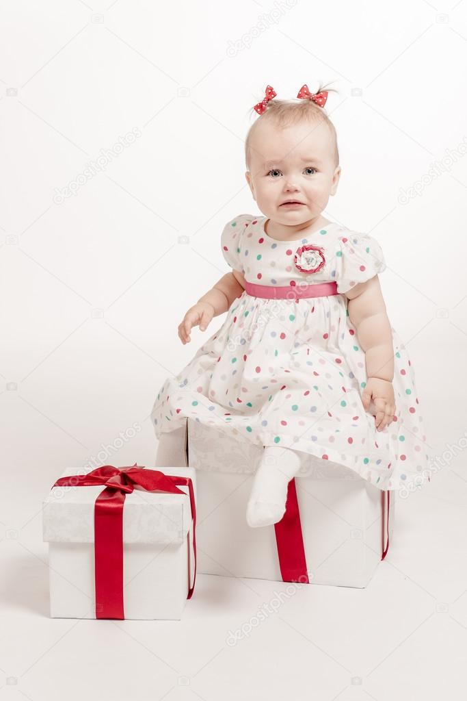 Lovely crying baby girl with two gift boxes over white background — Stock Photo #14657713