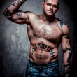 Muscular young man with many tattoos — Stock Photo