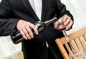 Man pouring red wine from bottle into a glass — Stock Photo
