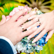 Wedding bouquet and hands of the bride and groom — Stock Photo