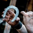 Blacksmith's dirty hands holding horseshoe - Stock Photo