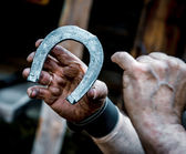 Blacksmith's dirty hands holding horseshoe — Stock Photo