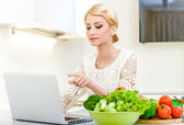 Woman looking for a recipe on the computer in the kitchen — Stock Photo