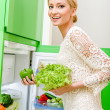 Stock Photo: Smiling young womtaking vegetables out of fridge
