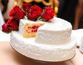 赤いバラで飾られた結婚式のケーキ — ストック写真