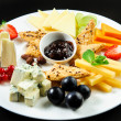 Platter with different types of cheese, fresh fruits and sauce — Stock Photo