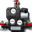 Central heating manifold over white wall - Stock Photo