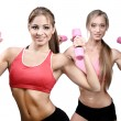 Two beautiful young women doing fitness exercise with dumbbells - Stock Photo