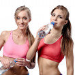 Two beautiful young women drinking water after fitness exercise — Foto de Stock