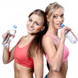 Royalty-Free Stock Photo: Two beautiful young women drinking water after fitness exercise