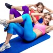 Two beautiful girls doing abdominal exercise - Stockfoto