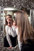 Beautiful young female applying lipstick looking at mirror — Stock Photo