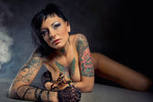 Beautiful woman with many tattoos posing indoors — Stock Photo