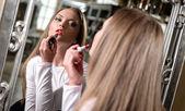 Mooie jonge vrouwelijke lippenstift spiegel kijken toe te passen — Stockfoto