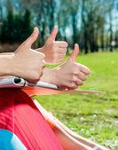 Estudiantes con los pulgares al aire libre — Foto de Stock