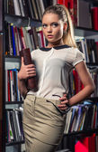 Elegant beautiful female student at the library — Stock Photo