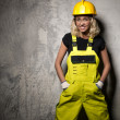 Attractive builder woman posing against grunge wall — Stock Photo