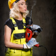 Attractive builder woman with a drill in her hands — Stock Photo #26083159