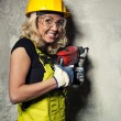 Attractive builder woman with a drill in her hands — Stock Photo #26083185