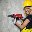 Attractive builder woman with a drill in her hands — Stock Photo #26083193