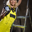 Attractive builder woman with a hammer and ladder indoors — Stock Photo #26083231
