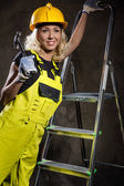 Attractive builder woman with a hammer and ladder indoors — Stock Photo