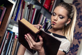 Female student at the library holding a book — Stock Photo