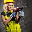 Attractive builder woman with a drill in her hands — Stock Photo