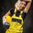 Tired builder woman with hammer and helmet indoors — Stock Photo
