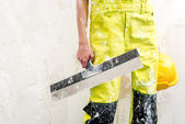 Construction worker with putty knife over obsolete background — Stock Photo