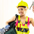 Smiling female construction worker with tool bag posing indoors — Stock Photo