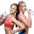 Two beautiful young women drinking water after fitness exercise — Stock Photo