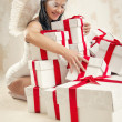 Beautiful young woman as angel with heap of gift boxes — Stock Photo